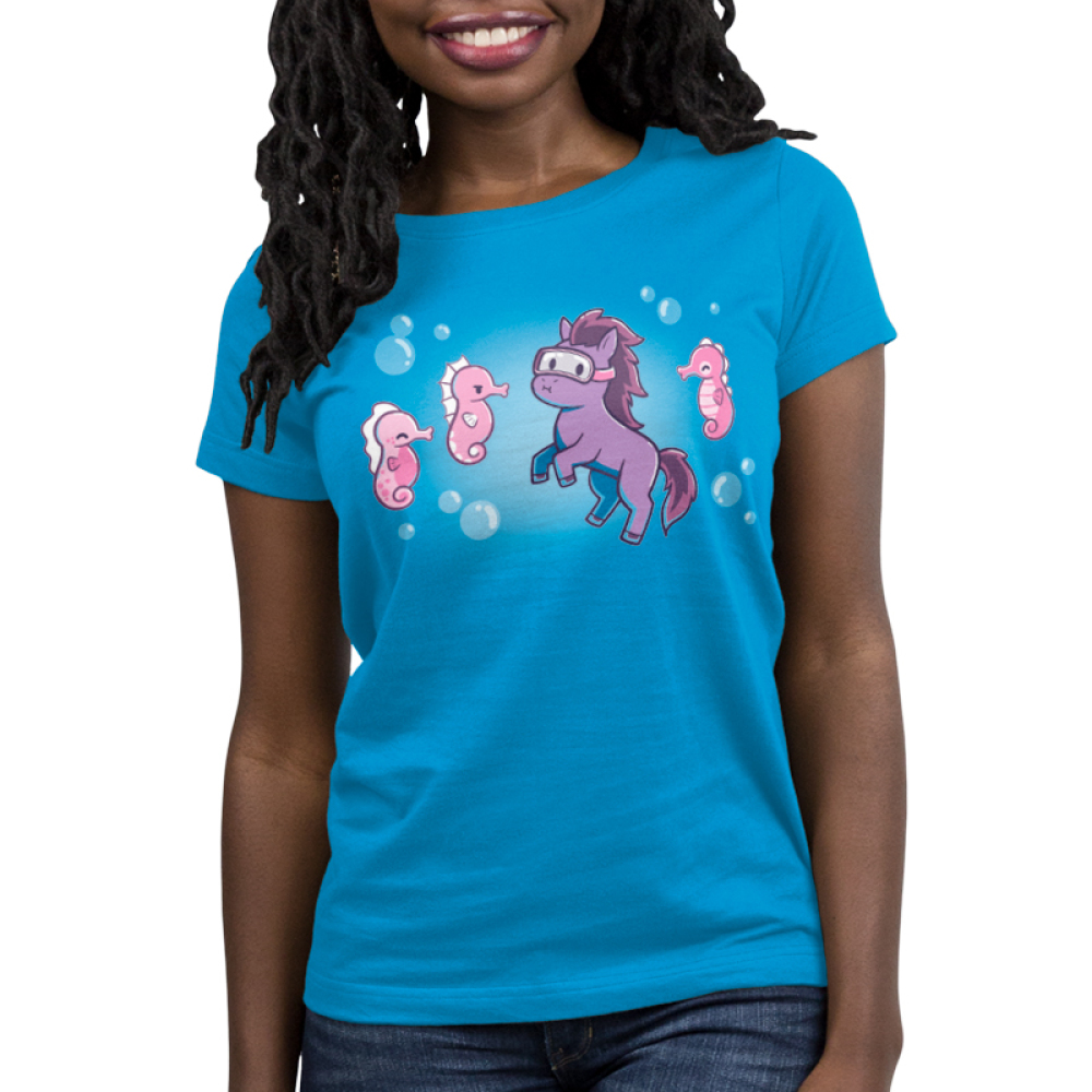 Seahorses women's T-shirt model TeeTurtle blue t-shirt featuring a purple horse wearing goggles and holding his breath under the sea while three pink seahorses swim around him. One of them looks mad.
