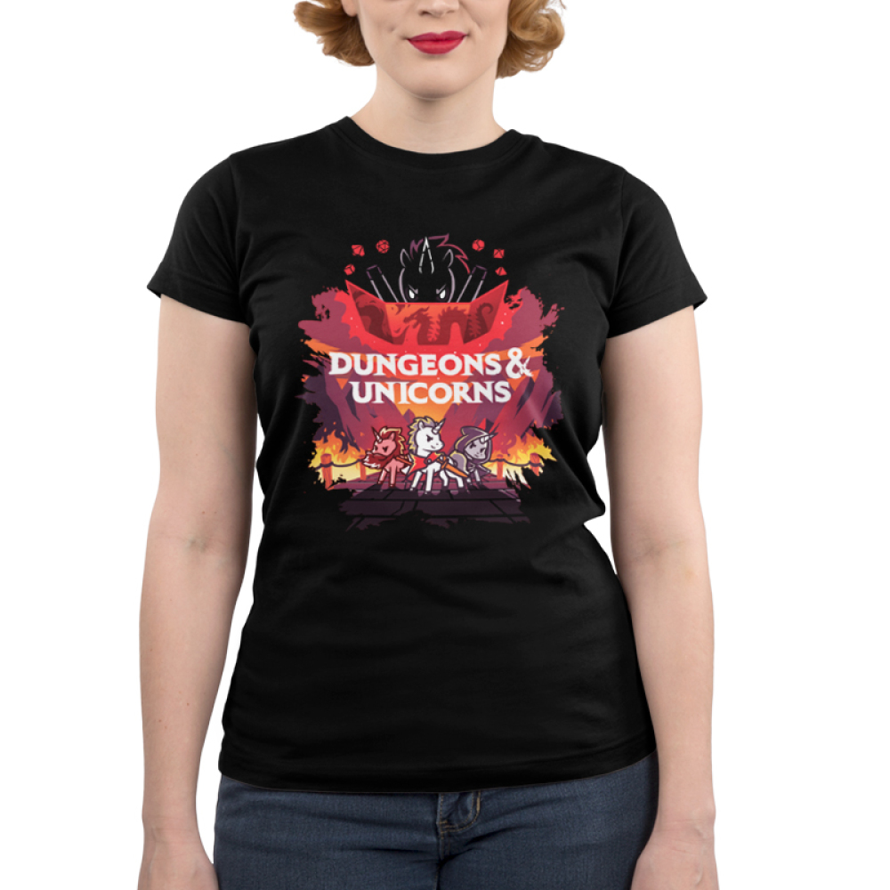 Dungeons and Unicorns (V2) juniors t-shirt model TeeTurtle black t-shirt featuring 3 unicorns with a flaming game set up and a larger unicorn behind them with shirt text