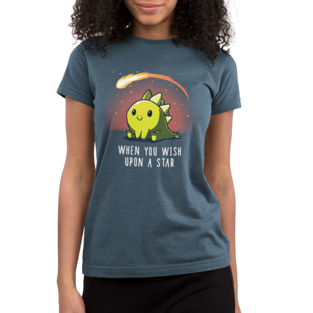 When You Wish Upon a Star Junior's t-shirt model TeeTurtle indigo t-shirt featuring a dinosaur sitting in the grass with a meteor flying by