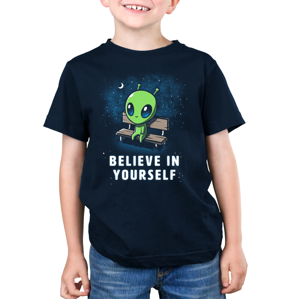 Believe in Yourself! Kid's t-shirt model TeeTurtle navy t-shirt featuring an alien sitting on a bench surrounded by stars and the moon