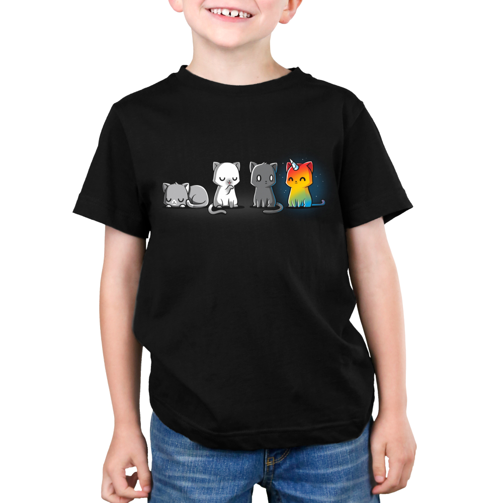 Meows & Magic Kid's t-shirt model TeeTurtle black t-shirt featuring four cats - one laying down, one licking its paw, one looking scared, and one rainbow kittencorn