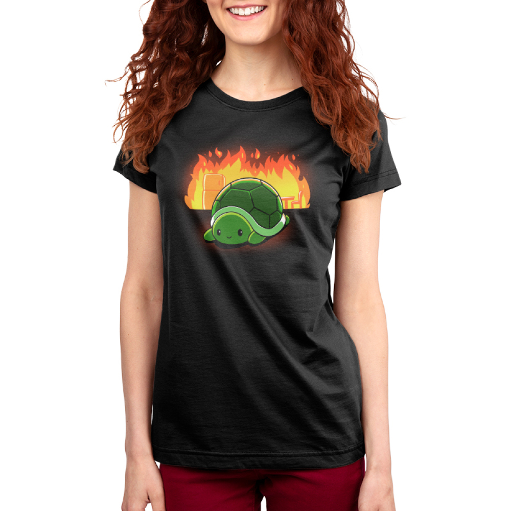 This is Fine Women's t-shirt model TeeTurtle black t-shirt featuring a turtle with a chair and refrigerator on fire behind him