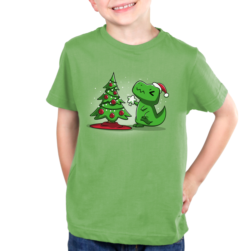 Christmas T-Rex Kid's t-shirt model TeeTurtle apple green t-shirt featuring a t-rex trying to get the star on top of the christmas tree