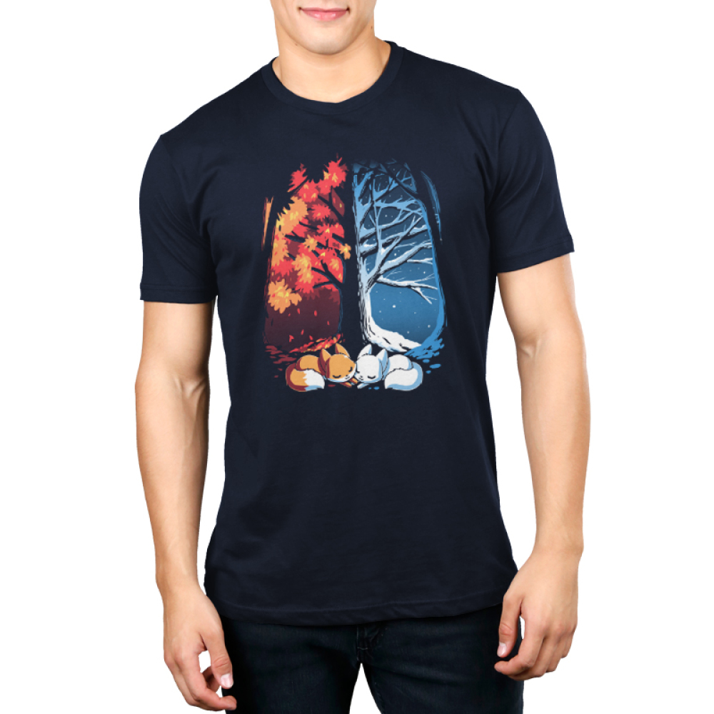 Fall & Winter Foxes Men's t-shirt model TeeTurtle navy t-shirt featuring a large tree with one side covered in snow and the other side covered in orange autumn leaves with two foxes laying underneath it, one orange and one white
