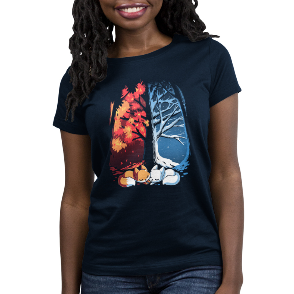Fall & Winter Foxes Women's t-shirt model TeeTurtle navy t-shirt featuring a large tree with one side covered in snow and the other side covered in orange autumn leaves with two foxes laying underneath it, one orange and one white