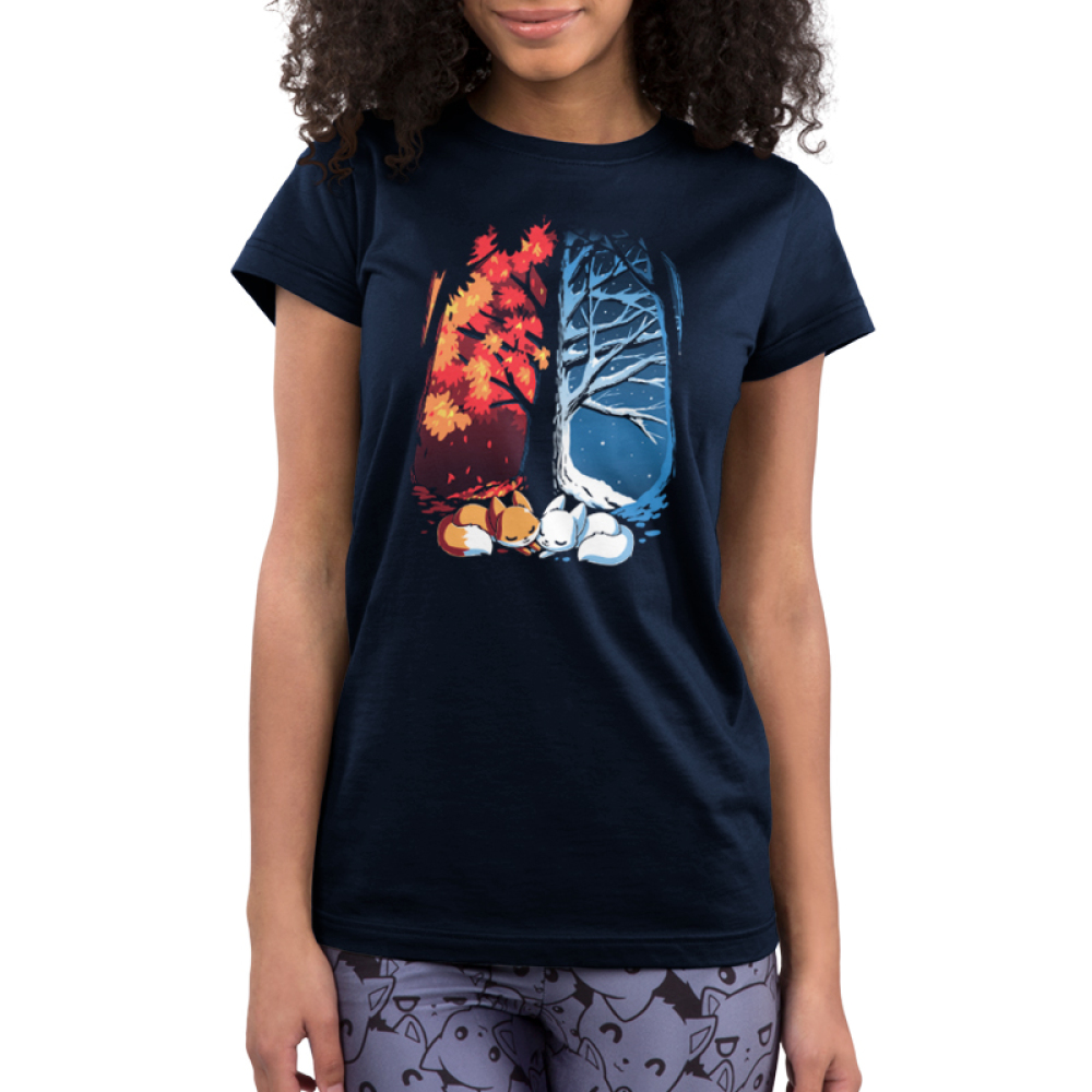 Fall & Winter Foxes Junior's t-shirt model TeeTurtle navy t-shirt featuring a large tree with one side covered in snow and the other side covered in orange autumn leaves with two foxes laying underneath it, one orange and one white