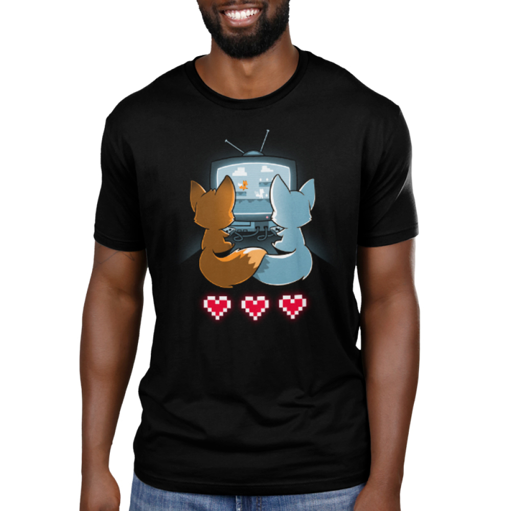 Fur the Love of Gaming Men's t-shirt model TeeTurtle black t-shirt featuring an orange and a blue fox sitting in front of a TV gaming together while holding their tails together with three video game hearts on the floor behind them