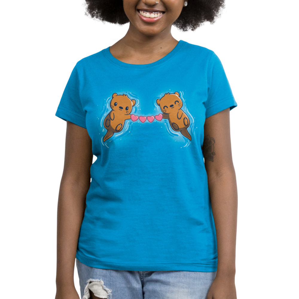 Love Like No Otter Women's t-shirt model TeeTurtle cobalt blue t-shirt featuring two otters smiling on their backs in blue water holding a chain of hearts between them