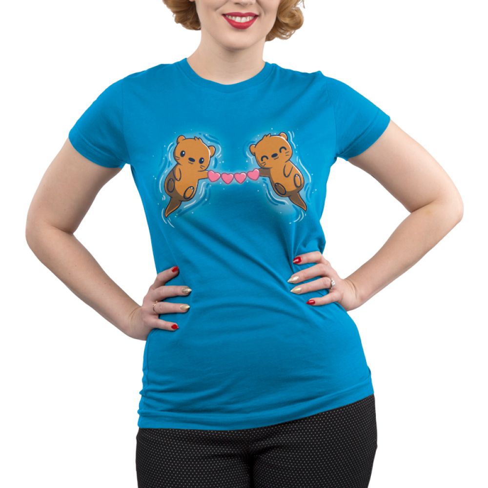 Love Like No Otter Junior's t-shirt model TeeTurtle cobalt blue t-shirt featuring two otters smiling on their backs in blue water holding a chain of hearts between them