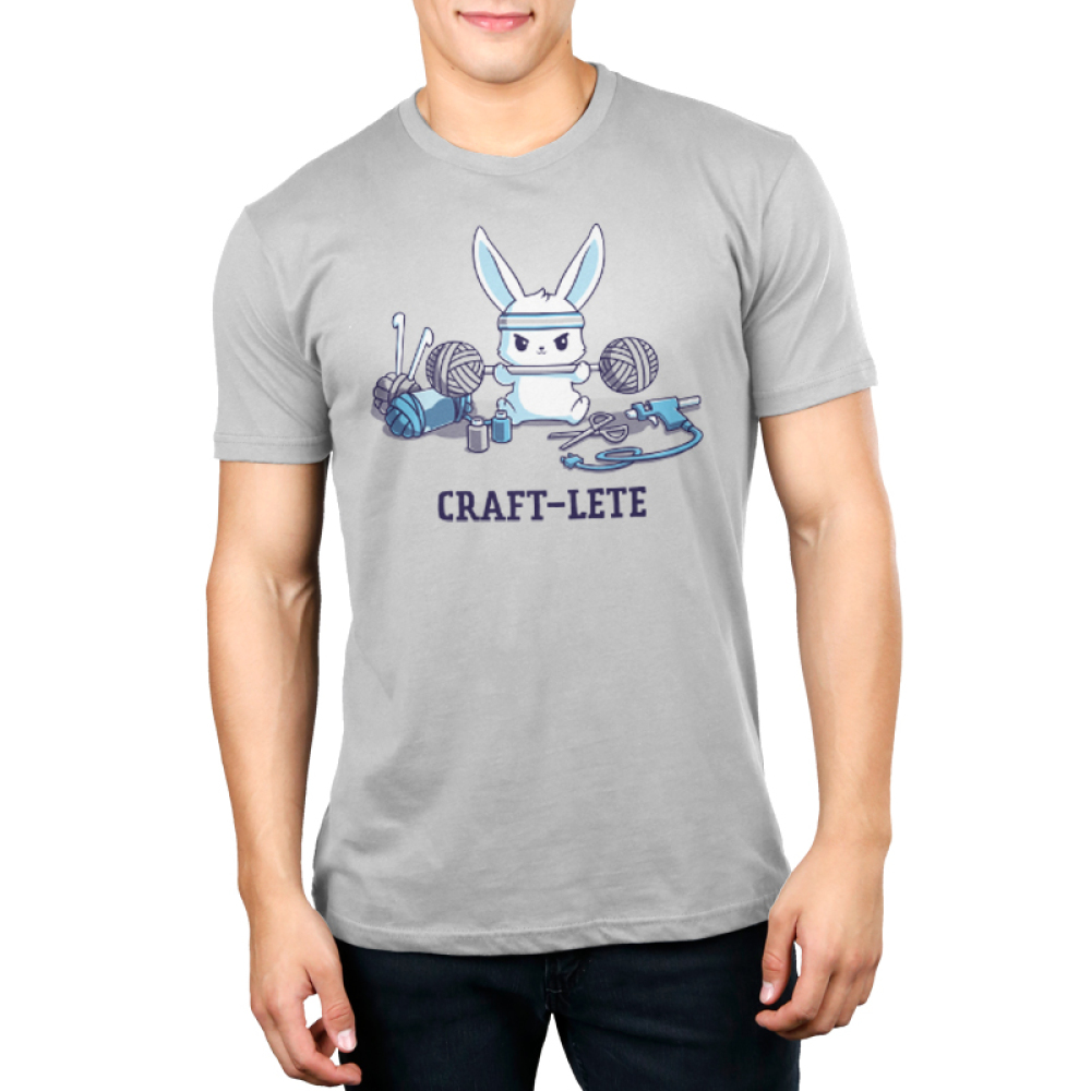 Craft-lete Men's t-shirt model TeeTurtle silver t-shirt featuring a bunny in a gray sweatband lifting two balls of yarn on either end of a fitness bar with yarn, a glue gun, scissors, and paint sitting around him