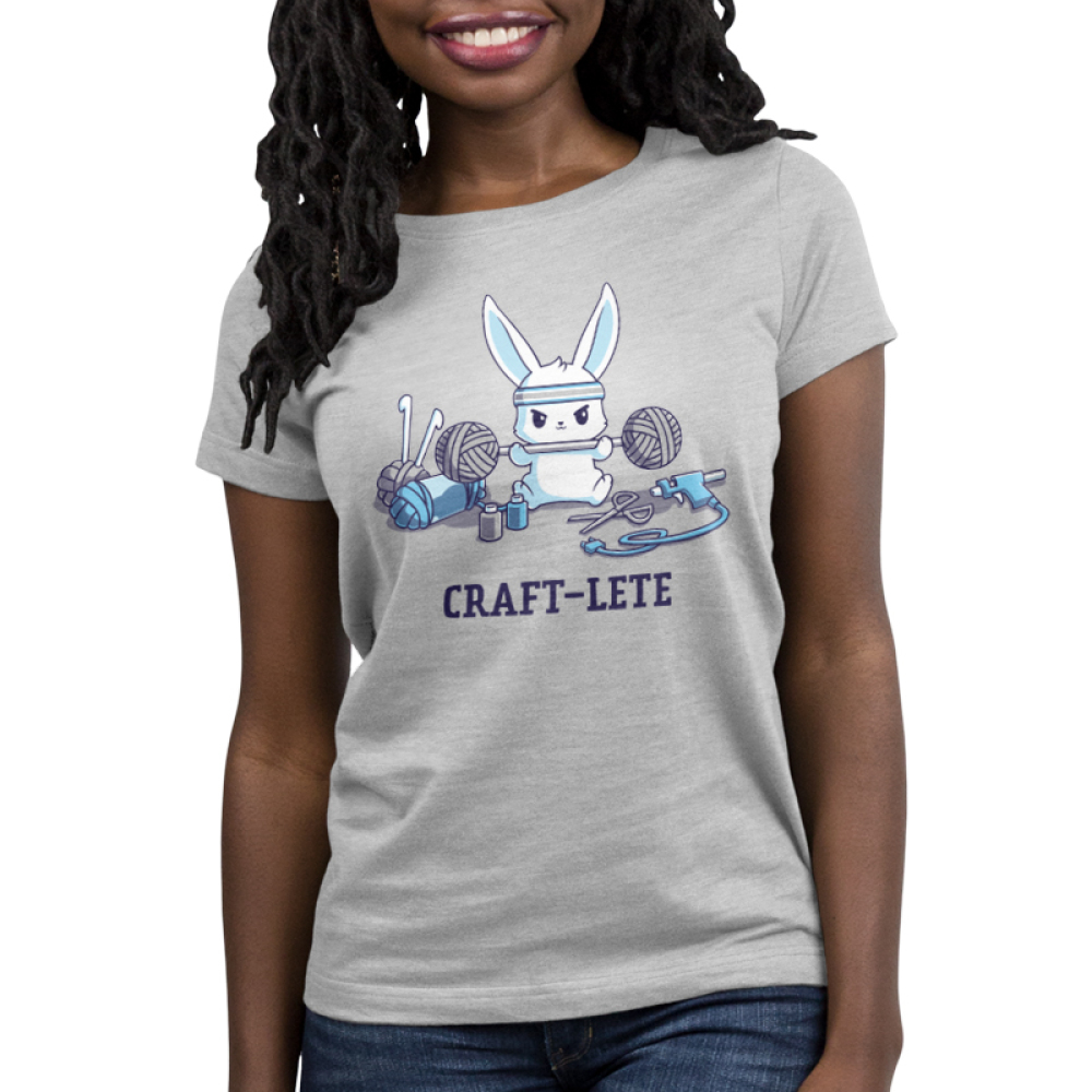 Craft-lete Women's t-shirt model TeeTurtle silver t-shirt featuring a bunny in a gray sweatband lifting two balls of yarn on either end of a fitness bar with yarn, a glue gun, scissors, and paint sitting around him