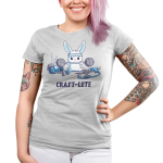 Craft-lete Junior's t-shirt model TeeTurtle silver t-shirt featuring a bunny in a gray sweatband lifting two balls of yarn on either end of a fitness bar with yarn, a glue gun, scissors, and paint sitting around him