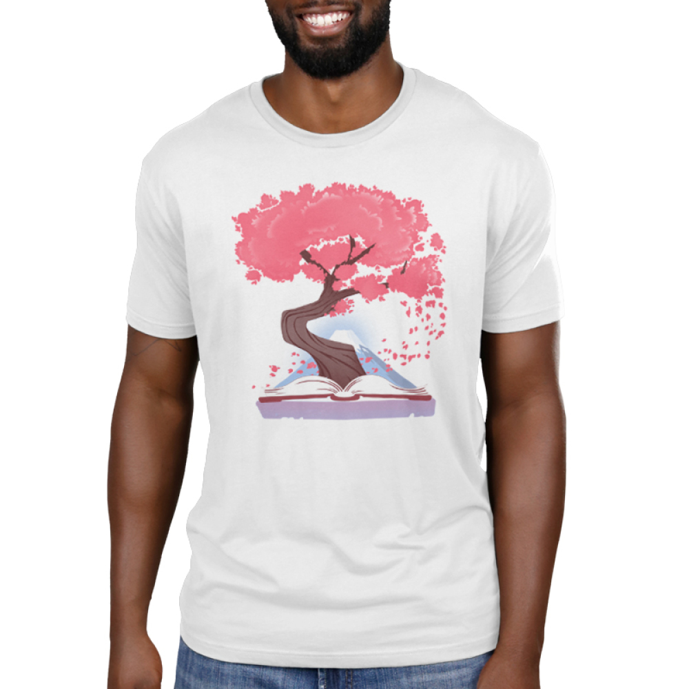 Blossoming Story Men's t-shirt model TeeTurtle white t-shirt featuring a tree with pink leaves coming out of an open book with a mountain in the background