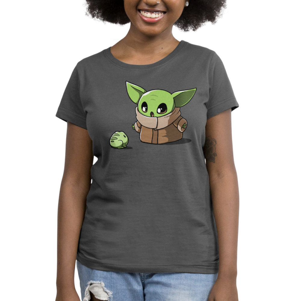 Snack Time Women's t-shirt model officially licensed Star Wars charcoal t-shirt featuring the child from the mandalorian staring at a little frog