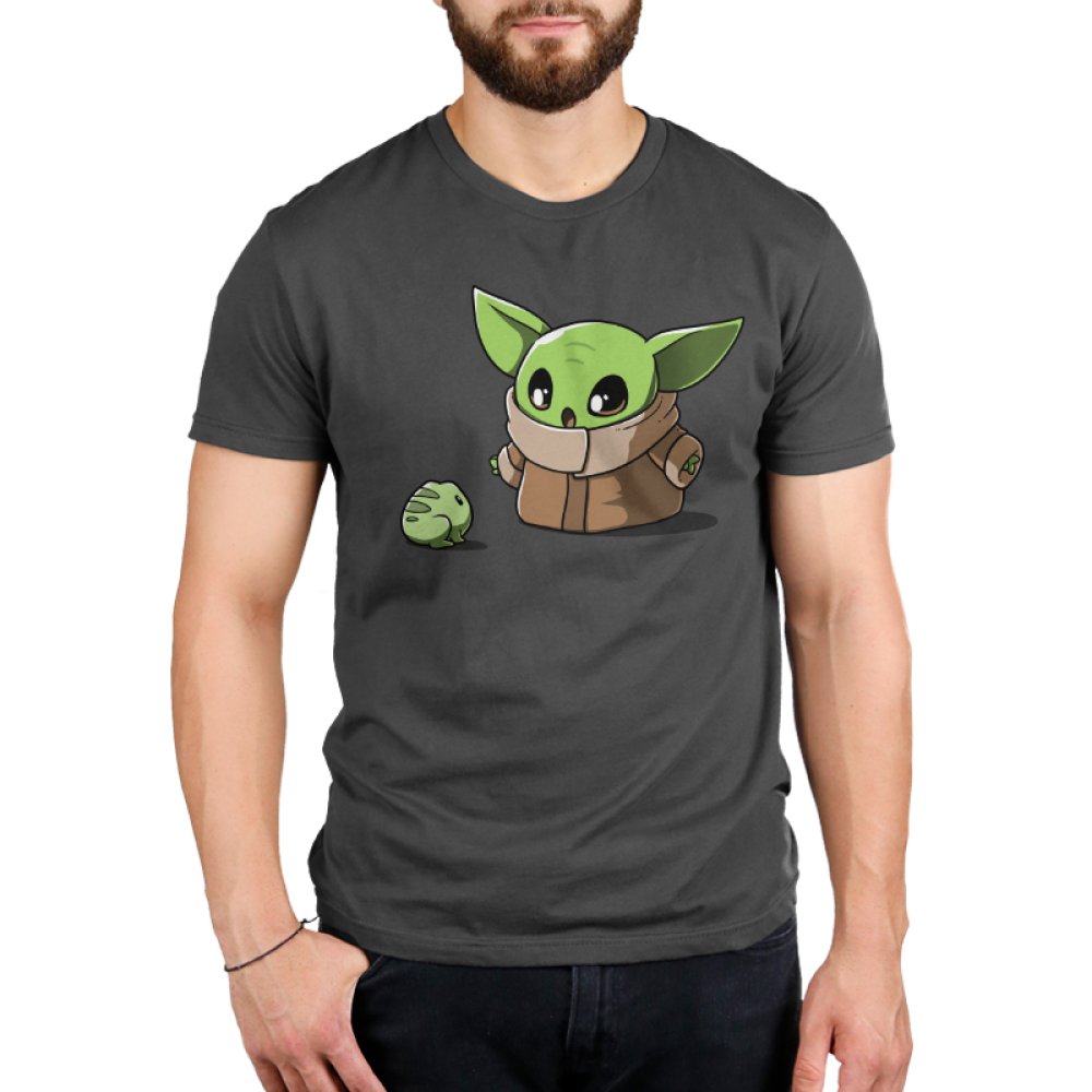 Snack Time Men's t-shirt model officially licensed Star Wars charcoal t-shirt featuring the child from the mandalorian staring at a little frog