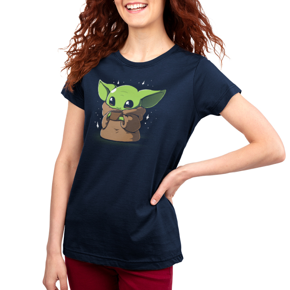 Sipping Soup Women's t-shirt model officially licensed Star Wars navy t-shirt featuring the child from the mandalorian sipping a cup of soup with stars around him