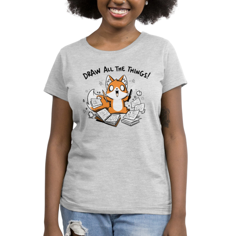 Draw All the Things Women's t-shirt model TeeTurtle light gray t-shirt featuring an excited looking fox with a pen in one hand and a pencil in the other surrounded by sketchbooks