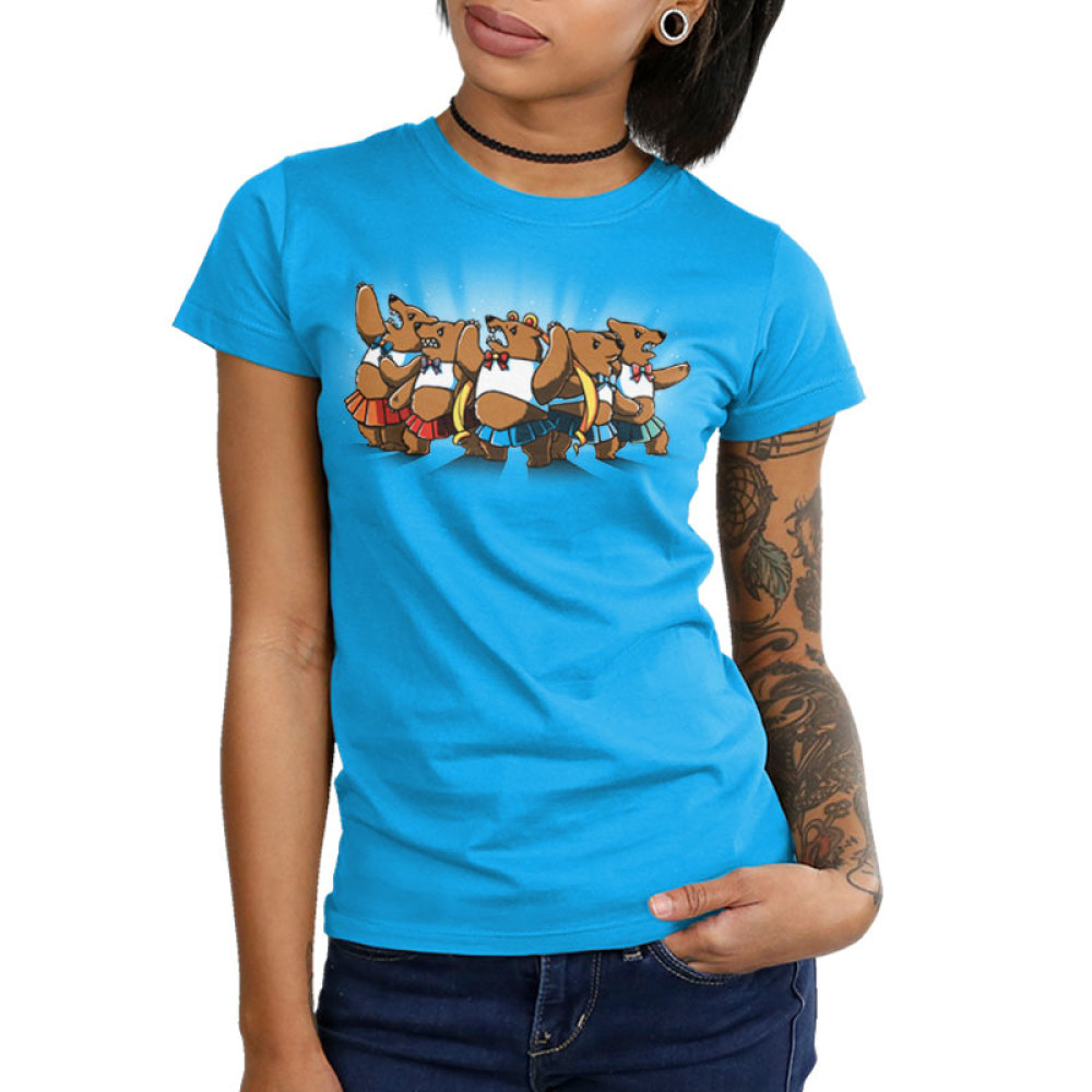 Astral Bears Junior's t-shirt model TeeTurtle cobalt blue t-shirt featuring a group of five sparkly, angry bears in fighting poses wearing white crop tops and bows and short pleated skirts in various colors, with the middle bear wearing long blonde ringlet pigtails.