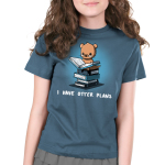 I Have Otter Plans Kid's t-shirt model TeeTurtle denim blue t-shirt featuring an otter in reading glasses holding open a big book while sitting on a pile of books