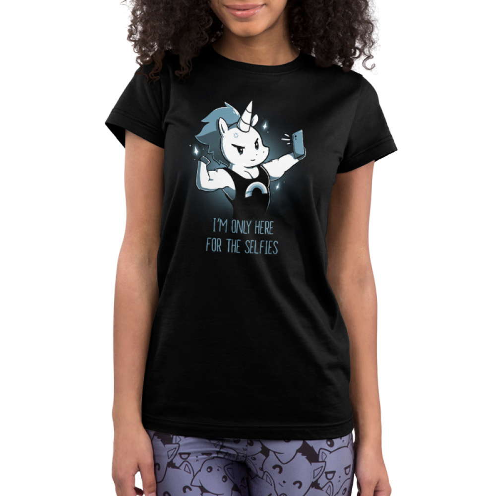 I'm Only Here for the Selfies Junior's t-shirt model TeeTurtle black t-shirt featuring a white unicorn with a short, dark blue mane wearing a tank top with a monochrome rainbow flexing his upper right limb while taking a selfie.