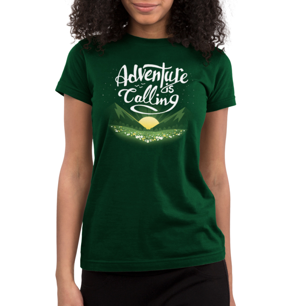 Adventure is Calling Junior's t-shirt model TeeTurtle forest green t-shirt featuring a sun rising in between green fields in front of a field of flowers