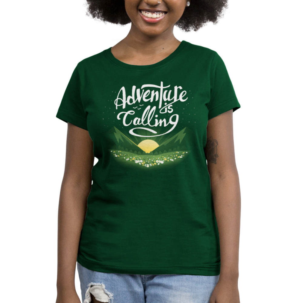 Adventure is Calling Women's t-shirt model TeeTurtle forest green t-shirt featuring a sun rising in between green fields in front of a field of flowers