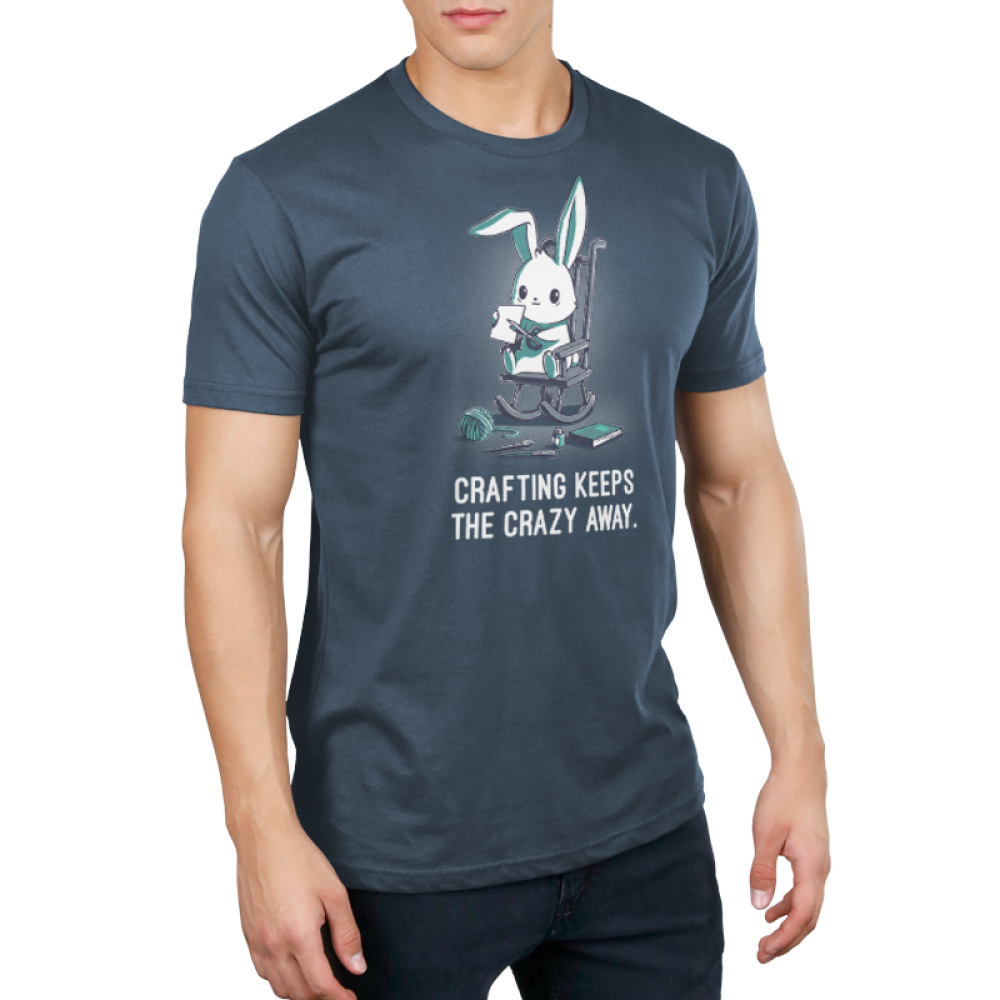 Crafting Keeps the Crazy Away Men's t-shirt model TeeTurtle indigo t-shirt featuring a wide eyed bunny on a rocking chair cutting a piece of paper with scissors with yarn, paint brushes, and books around him on the ground