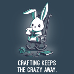 Crafting Keeps the Crazy Away t-shirt TeeTurtle indigo t-shirt featuring a wide eyed bunny on a rocking chair cutting a piece of paper with scissors with yarn, paint brushes, and books around him on the ground