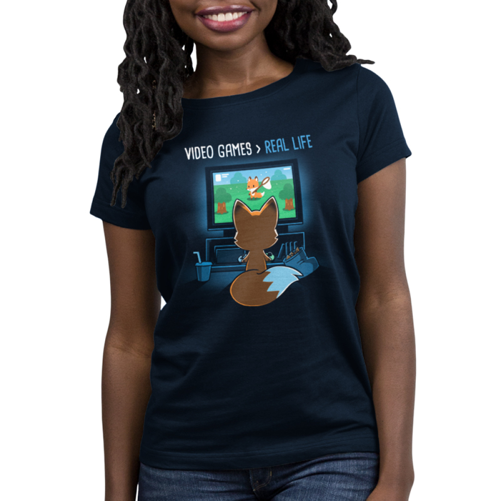 Video Games > Real Life Women's t-shirt model TeeTurtle navy t-shirt featuring the back of a fox who is facing a TV playing video games with a bag of chips and a drink next to him