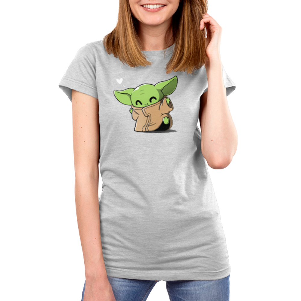 Happy Dance Women's t-shirt model officially licensed light gray Star Wars t-shirt featuring The Child from the Mandalorian doing a dance with a heart in the corner of the design
