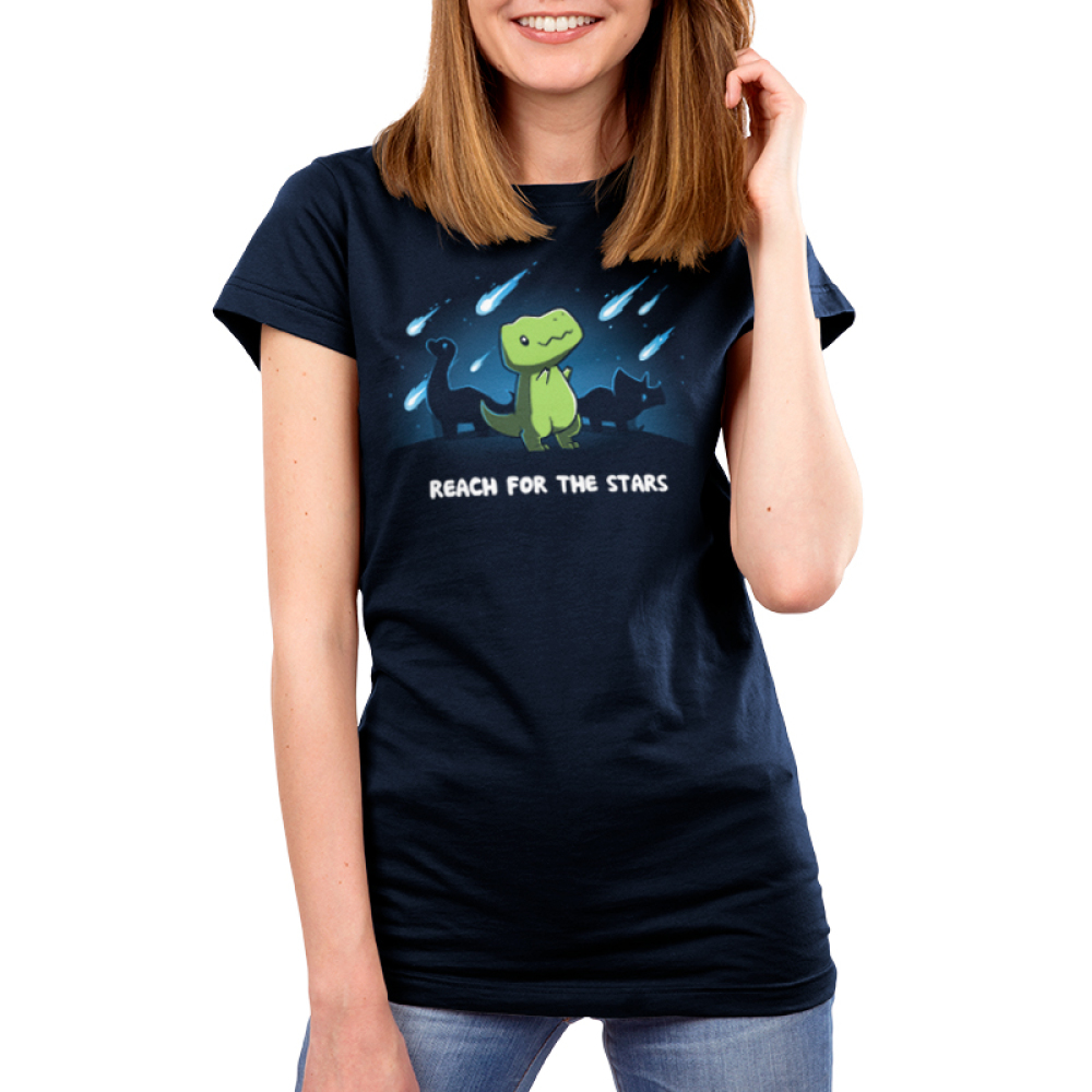 Reach for the Stars Women's t-shirt model TeeTurtle navy t-shirt featuring a green t-rex reaching for meteors falling in the sky with two dinosaurs behind him