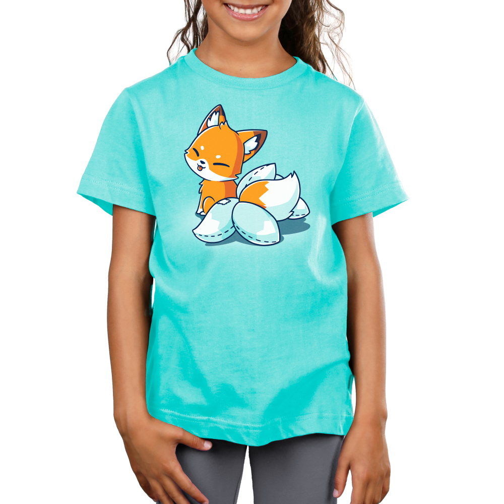 Kitsune Cosplay Kids t-shirt TeeTurtle Caribbean blue t-shirt featuring an orange fox with white on its moth and the tip of its tail, seated, facing away and looking back at you with its tongue poking out in a playful manner. It has 4 white fake tails attached to the real tail that have dashed lines along the edges to show that they were stitched together.