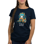 The Book Was Better (Cat) Women's t-shirt model TeeTurtle navy t-shirt featuring a white cat sitting on a big teal arm chair reading a book with stacks of books on either side of the chair