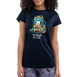 The Book Was Better (Cat) Junior's t-shirt model TeeTurtle navy t-shirt featuring a white cat sitting on a big teal arm chair reading a book with stacks of books on either side of the chair