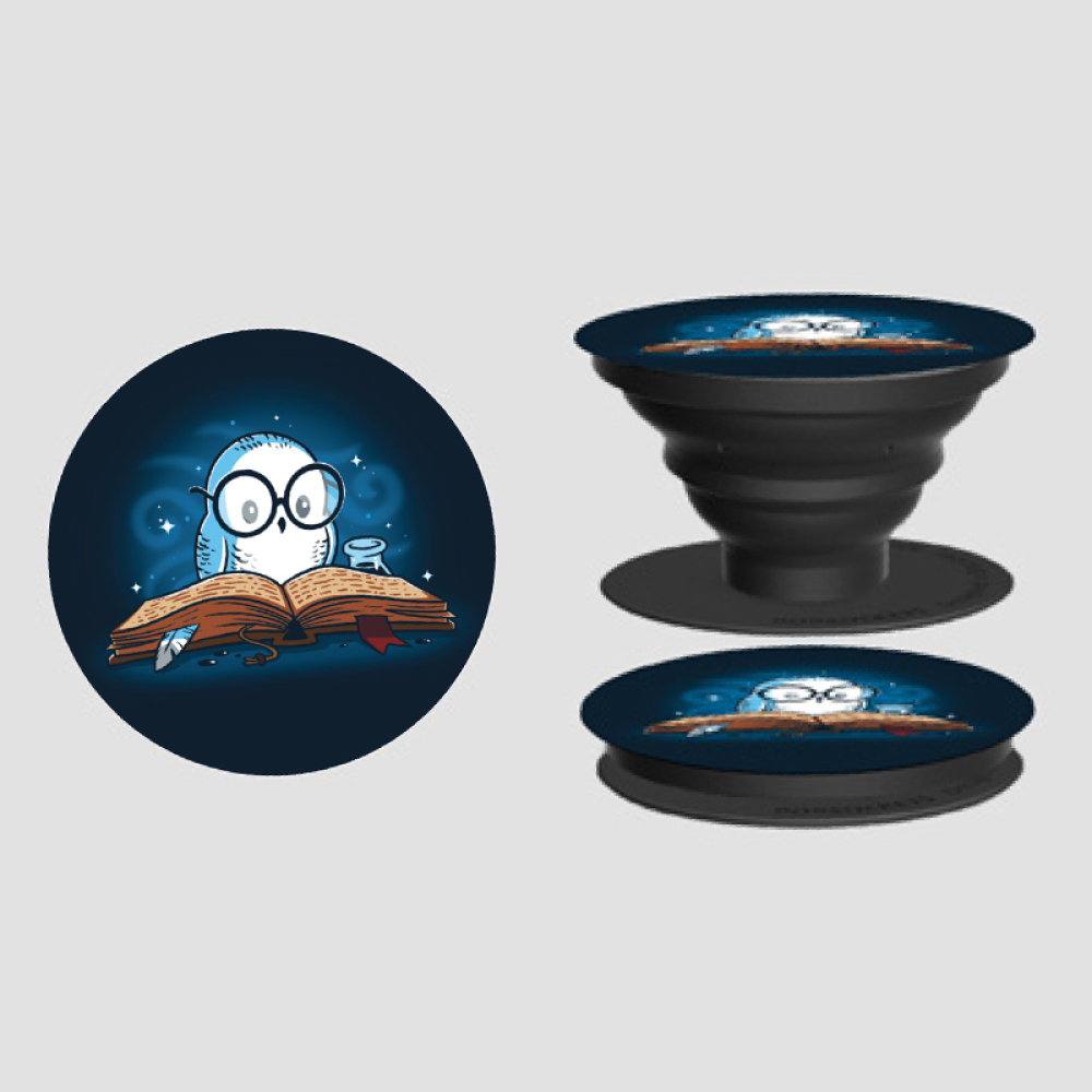 Reading is Magical PopSocket TeeTurtle navy PopSocket featuring a white owl in glasses with an old book open in front of his with sparkles behind him