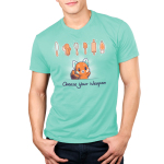 Choose Your Weapon (Baking) Men's t-shirt model TeeTurtle chill blue t-shirt featuring a cheerful looking red panda with its arms up and a knife, measuring spoons, whisk, spatula, rolling pin, and frosting bag lined up above him