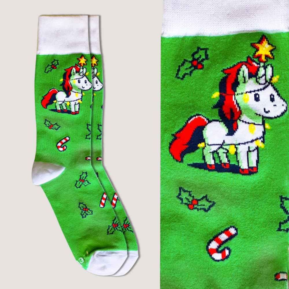 Christmas Unicorn Socks green socks featuring a white unicorn with red hair wrapped up in Christmas lights with a star on its horn with candy canes and holly plants all over the socks