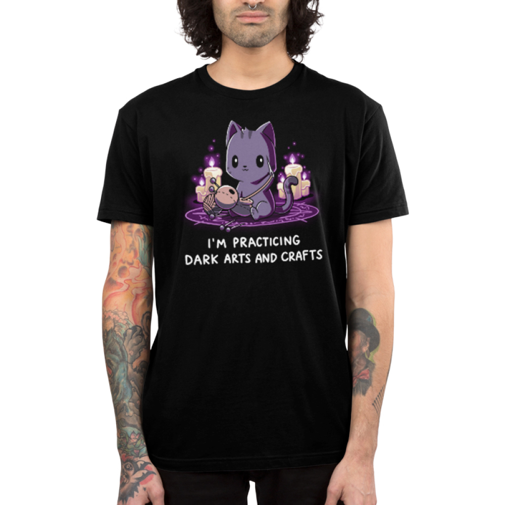 Dark Arts and Crafts Men's t-shirt model TeeTurtle black t-shirt featuring a dark purple cat sewing a voodoo doll with lit candles behind him