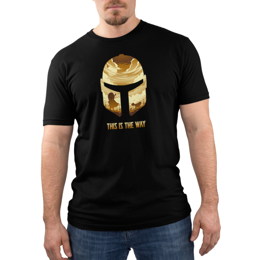 This is the Way Men's t-shirt model officially licensed black Star Wars t-shirt featuring the Mandalorian helmet and within that helmet are golden clouds, and the mandalorian with a desert scene behind him