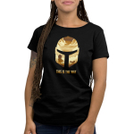 This is the Way Women's t-shirt model officially licensed black Star Wars t-shirt featuring the Mandalorian helmet and within that helmet are golden clouds, and the mandalorian with a desert scene behind him