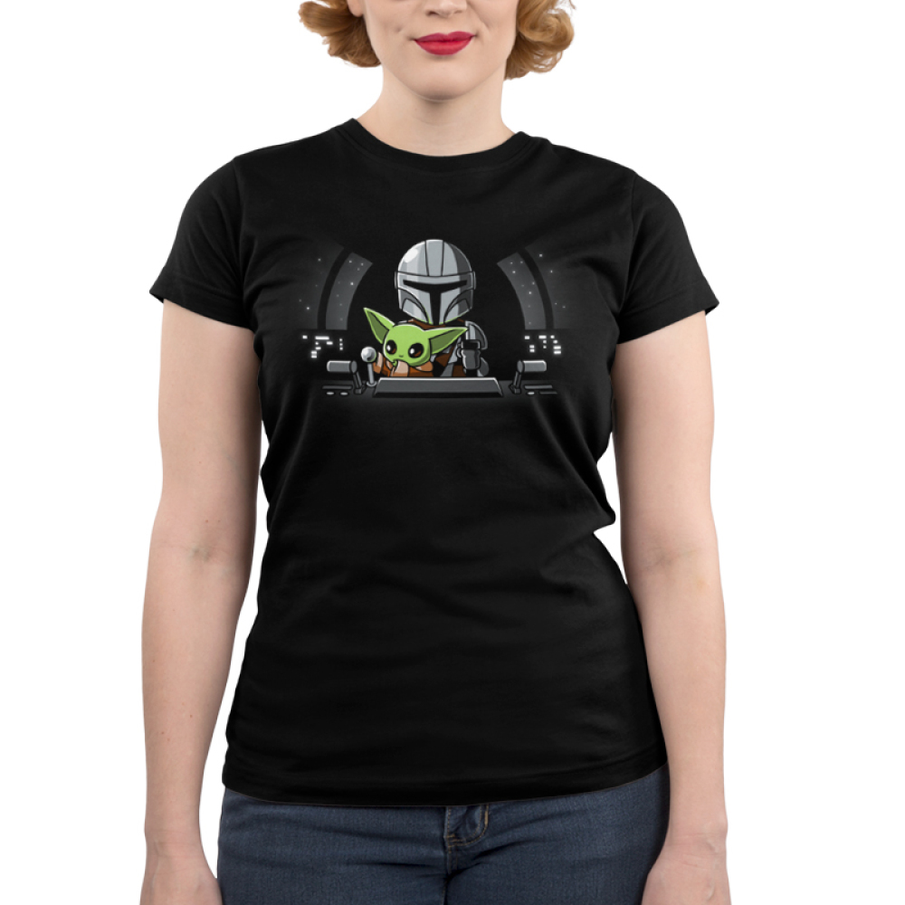 Co-Pilot Junior's t-shirt model officially licensed black Star Wars t-shirt featuring The Child reaching for a lever while sitting on Mando's lap in a spaceship