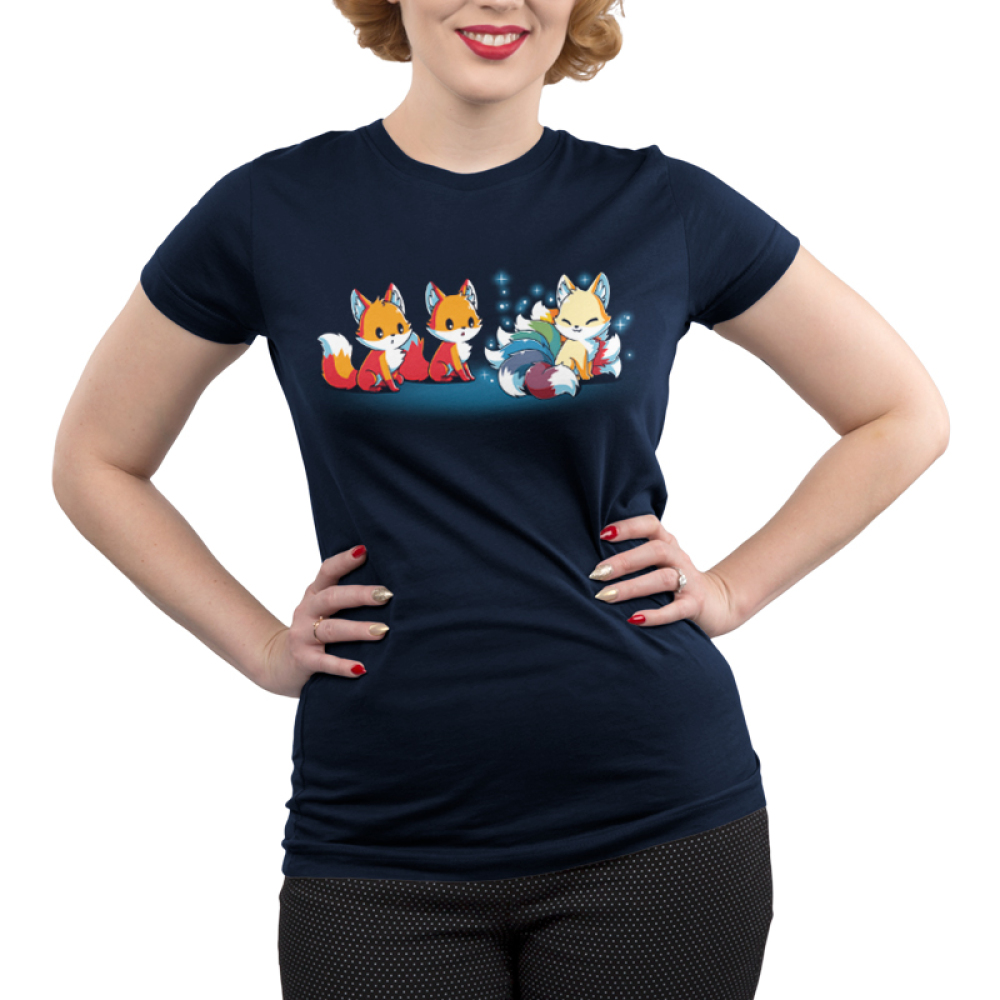 A Foxy Tail Junior's t-shirt model TeeTurtle navy t-shirt featuring two orange foxes staring at a light orange smiling kitsune with 9 sparkling rainbow tails