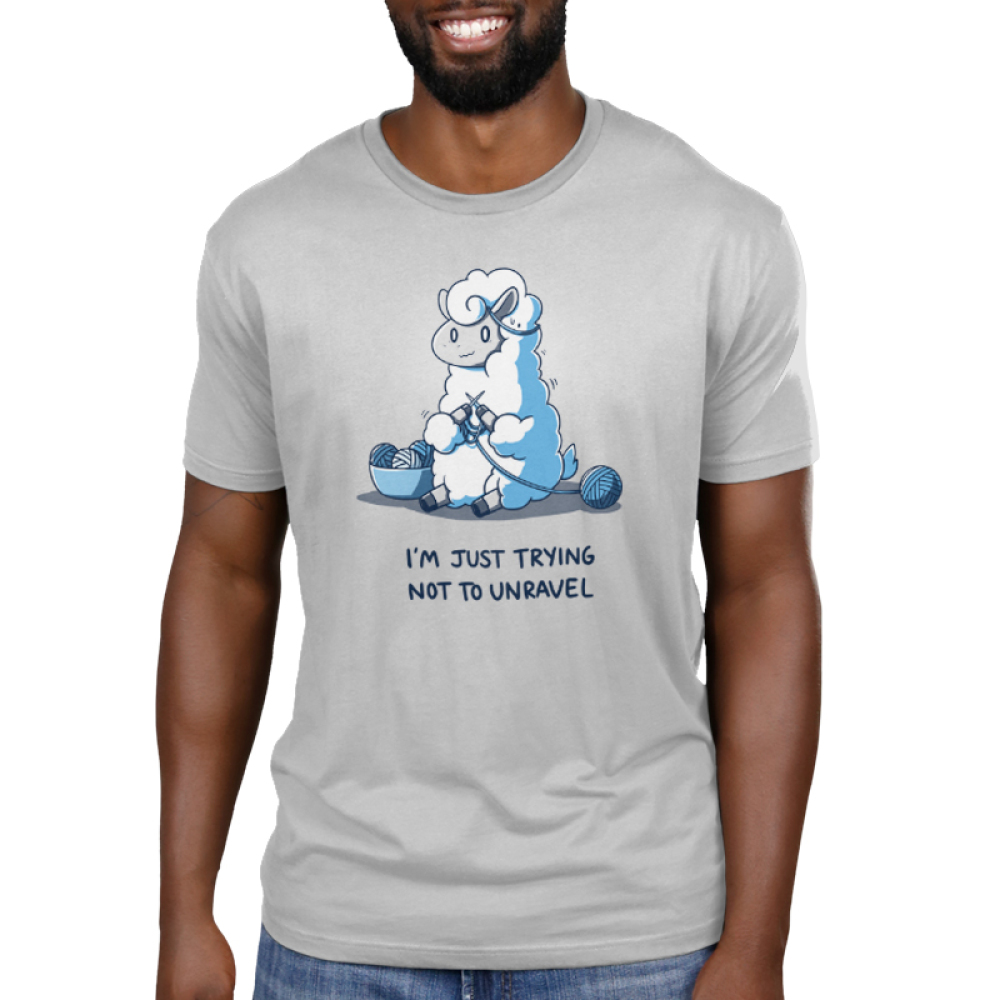 Trying Not to Unravel Men's t-shirt model TeeTurtle silver t-shirt featuring a llama sitting on the ground with a nervous looking face, knitting with blue yarn with a bowl of yawn next to him