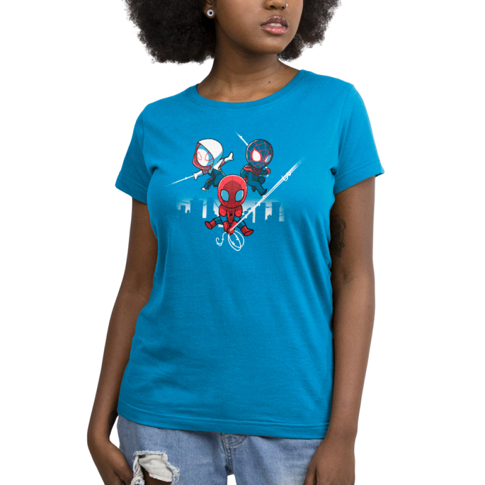 Spider People Women's t-shirt model officially licensed cobalt blue Marvel t-shirt featuring Spider Man in his red suit holding onto a spider web in the middle, and him in his white suit on the left and black suit on the right