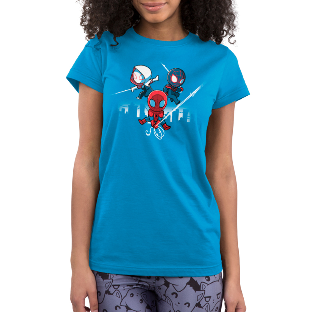 Spider People Junior's t-shirt model officially licensed cobalt blue Marvel t-shirt featuring Spider Man in his red suit holding onto a spider web in the middle, and him in his white suit on the left and black suit on the right