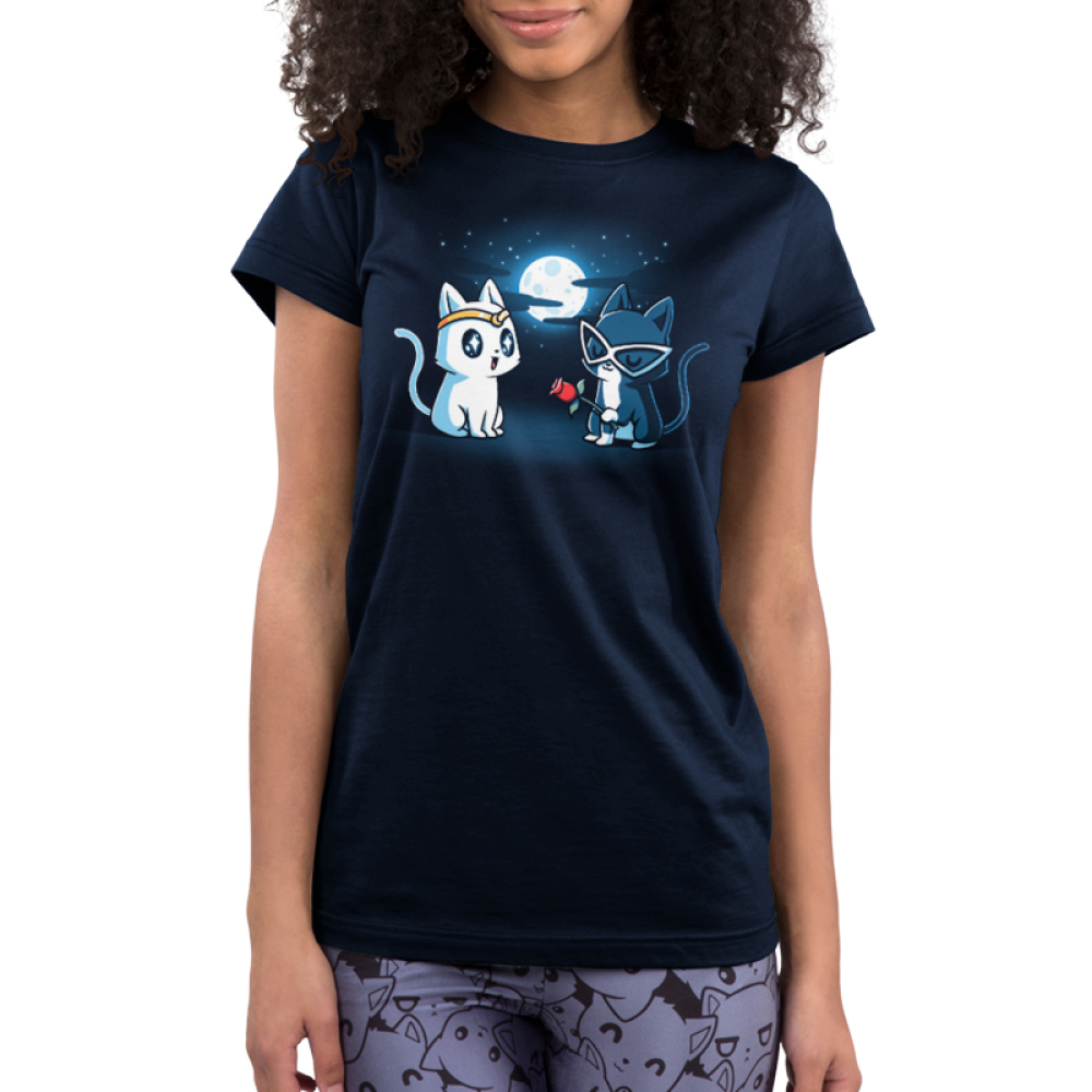 Star-Crossed Lovers Junior's t-shirt model TeeTurtle navy t-shirt featuring a white cat with a gold tiara all wide eyed looking at a black cat with big white glasses on holding a rose while they are outside in front of a full moon and stars