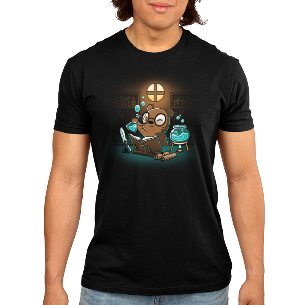 Potion Master Men's t-shirt model TeeTurtle black t-shirt featuring an otter with big round glasses holding up a potion flask with blue liquid and bubbles with an open book, scrolls, a feather pen, and a bowl with blue potion and a candle underneath it all in front of him