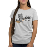Go Ahead, Bake My Day Women's t-shirt model TeeTurtle silver t-shirt featuring an angry looking gray cat with flour all over its face holding a dirty whisk with a rolling pin and bowl next to him