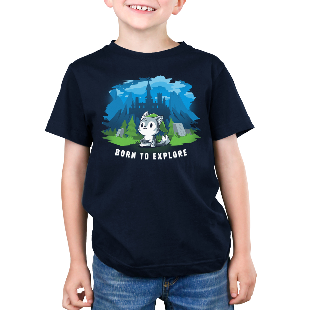 Born to Explore Kid's t-shirt model TeeTurtle navy t-shirt featuring a little wolf holding a video game remote with a green slouchy hat on with a fantasy landscape behind him - a castle, mountains, green grass