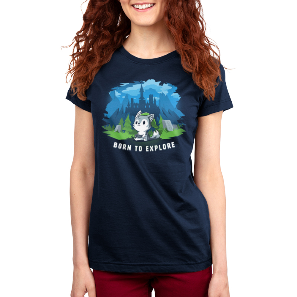 Born to Explore Women's t-shirt model TeeTurtle navy t-shirt featuring a little wolf holding a video game remote with a green slouchy hat on with a fantasy landscape behind him - a castle, mountains, green grass